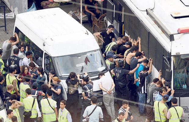 Taksim'de polisler göstericileri gözaltına alıyor. Manzara darbe dönemini hatırlatıyor