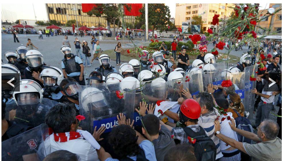 Ellerinde karanfil olan insanlara polisler gazla saldır. Foto: Reuters