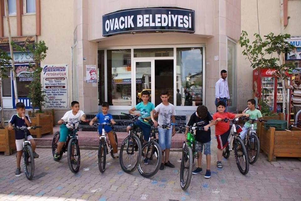 Çocuklar hem kitap okuyor hemde bisiklete binmenin keyfini yaşıyor.